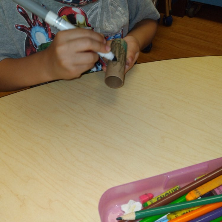 preschooler using marker to color cardboard tube
