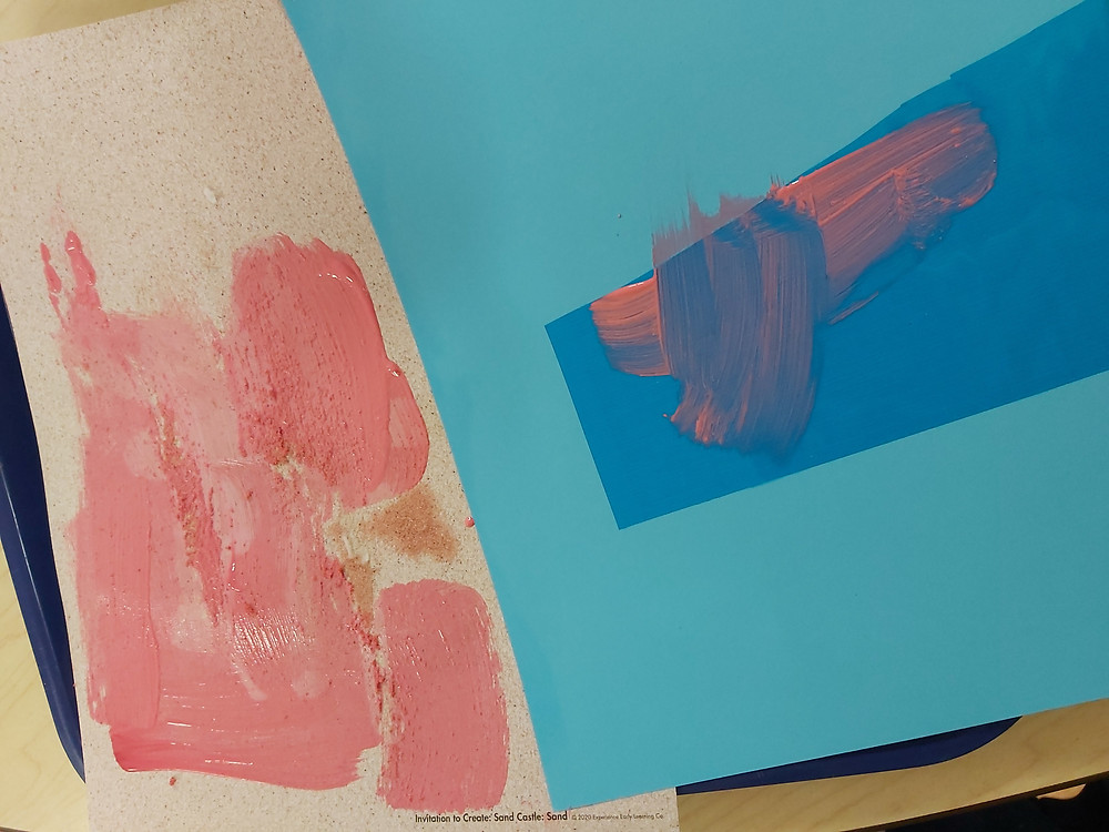 preschooler's process art with pink paint, sand and blue paper