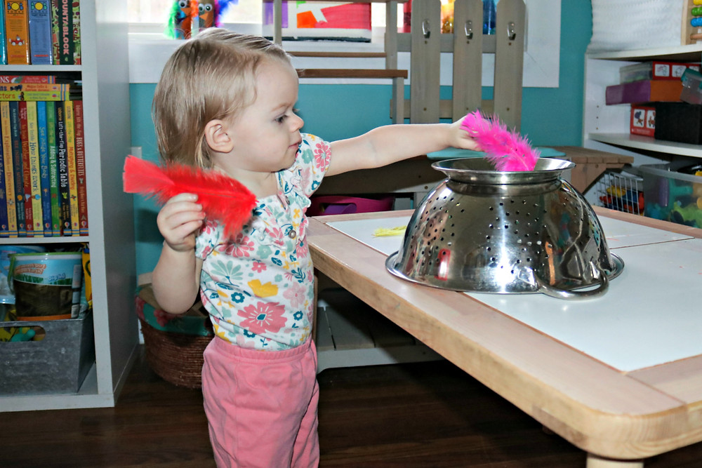 toddler putting feathers into an upside down strainer