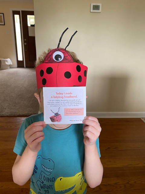 child wearing ladybug headband and holding description of project in front of face