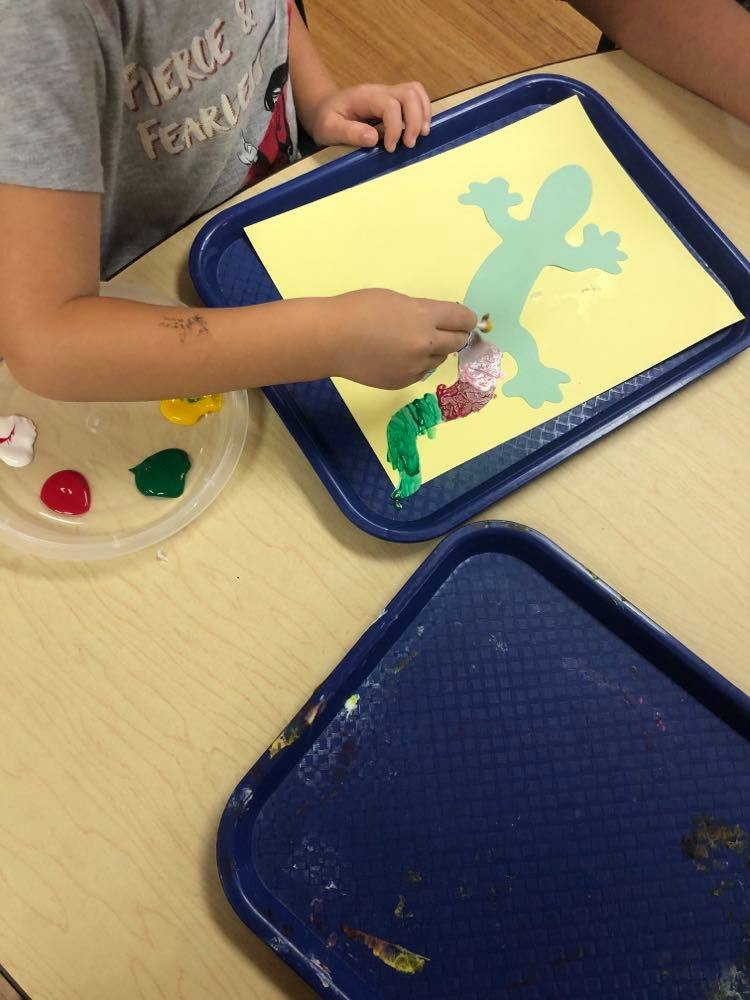 preschooler using cotton swab to make gecko art