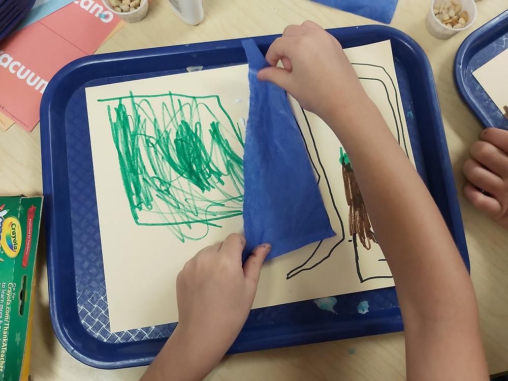 preschooler adding blue tissue paper to collage