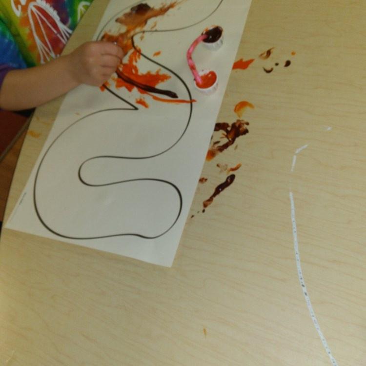 preschooler painting on worm outline