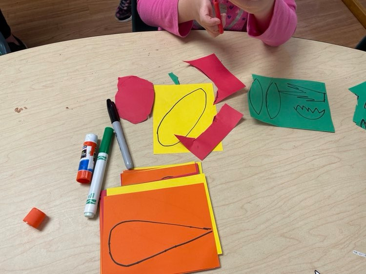 child cutting vegetable shapes out of cardstock