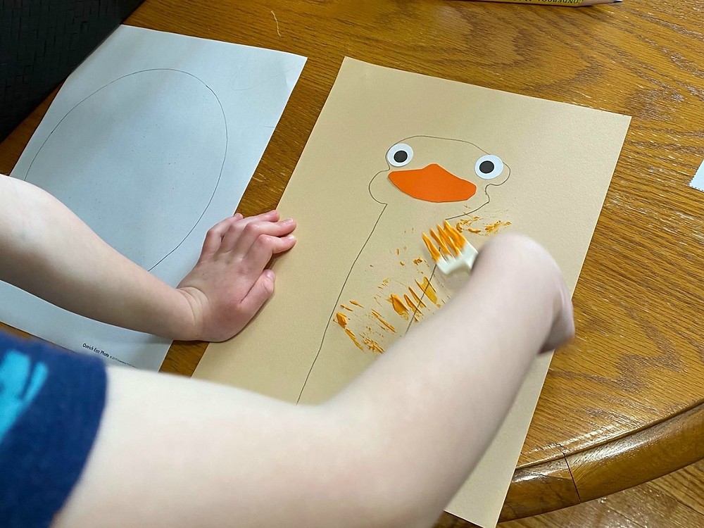 child making an ostrich using a fork, paint, and construction paper