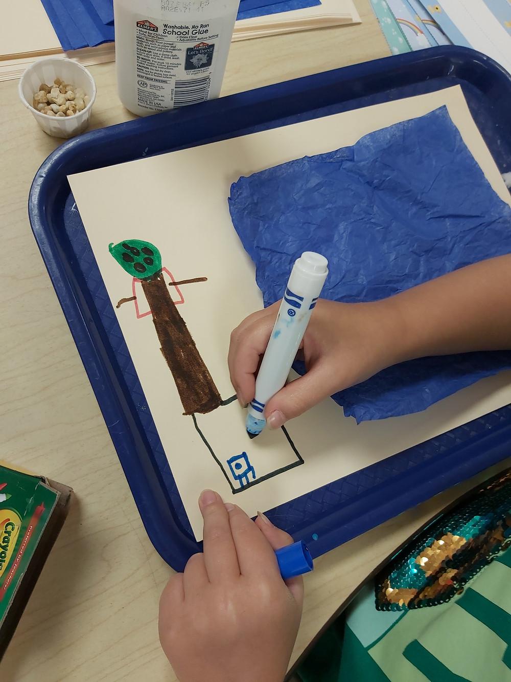 preschooler creating river collage