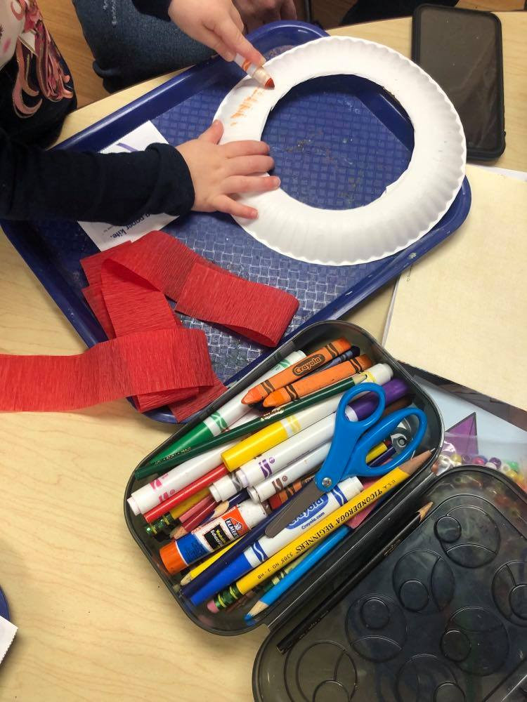 preschooler using marker to color on paper plate