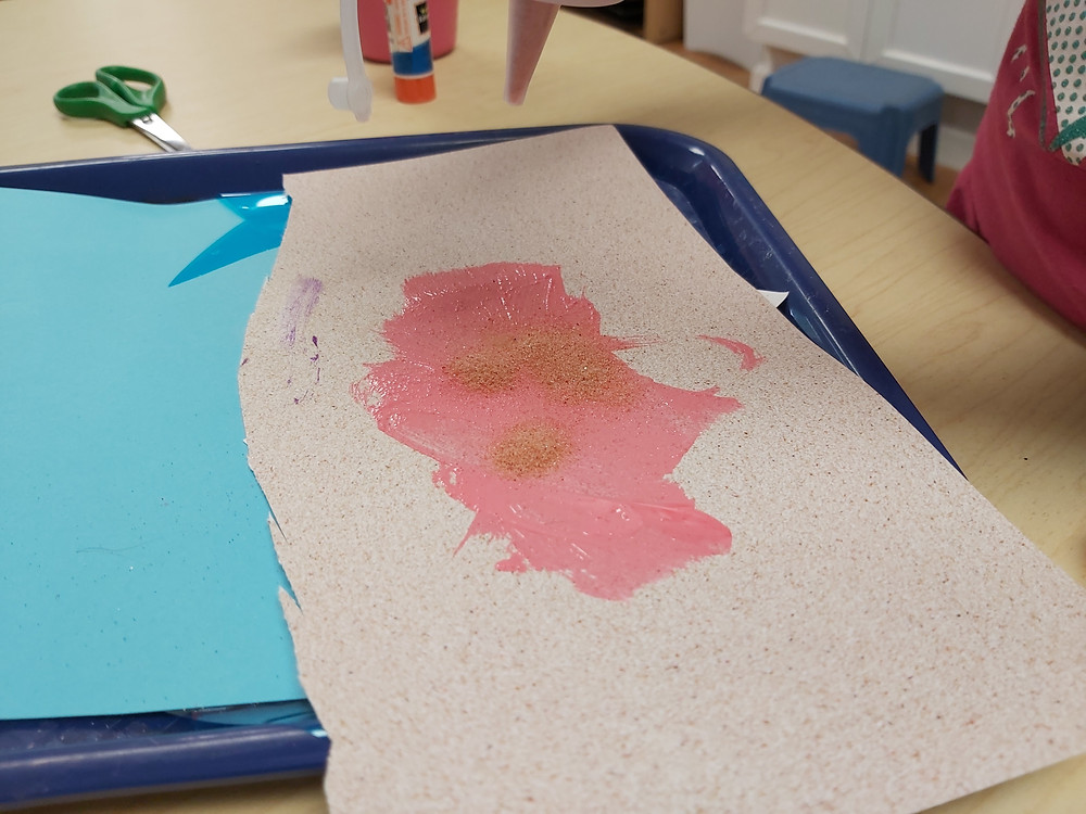preschooler adding pink sand to artwork