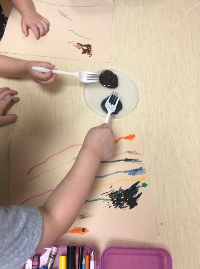 children using forks to add feathers to ostrich art