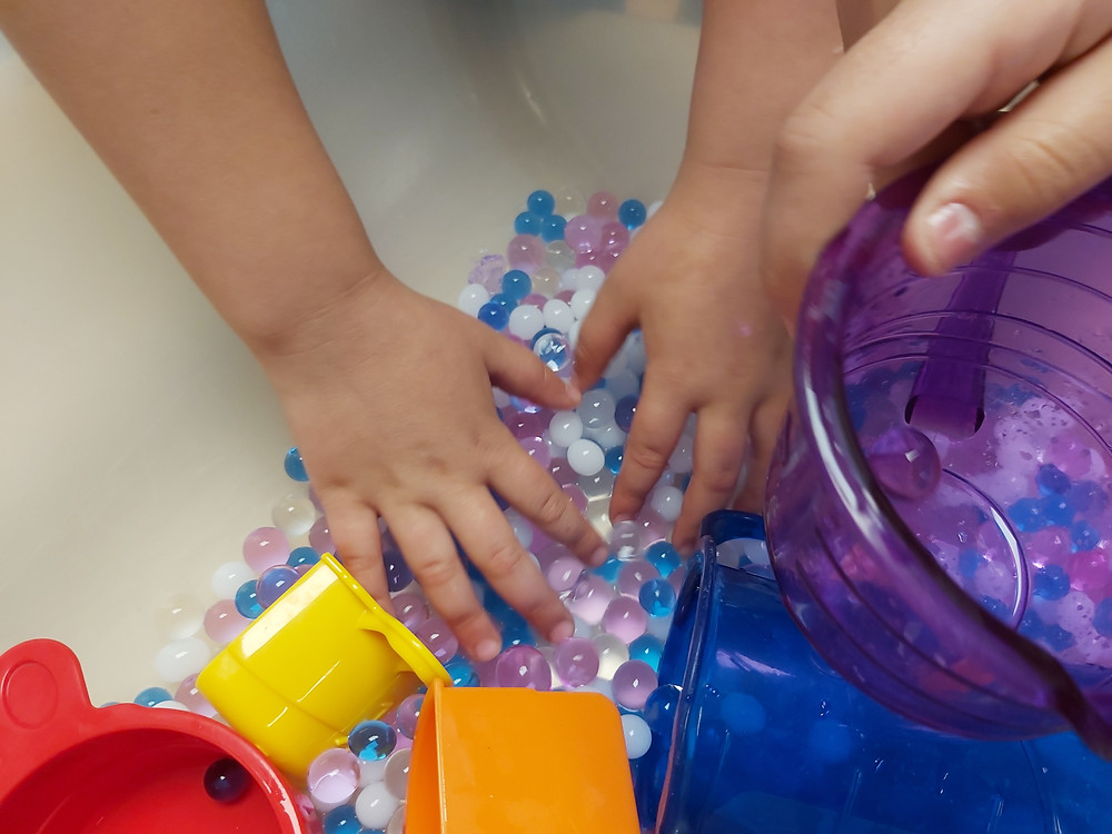 preschoolers playing with measuring cups and water beads