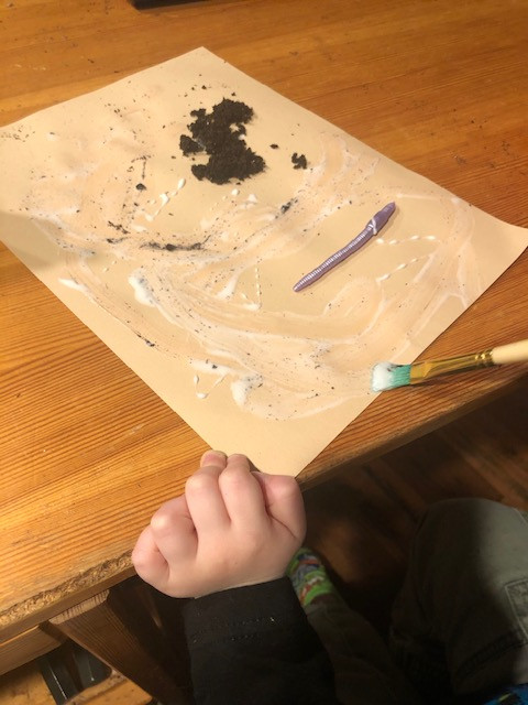 preschool making worm art by painting on a piece of cardstock