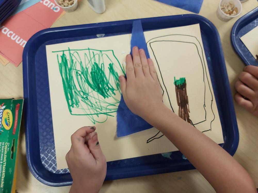 preschooler gluing blue tissue paper on collage