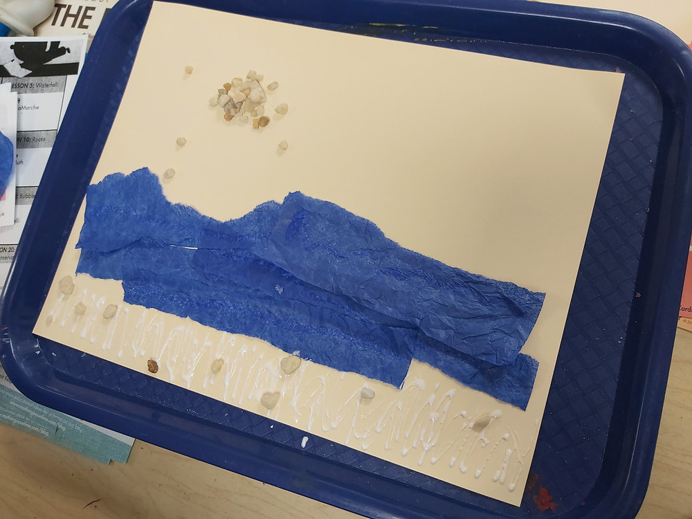 river collage artwork with blue tissue paper and small stones