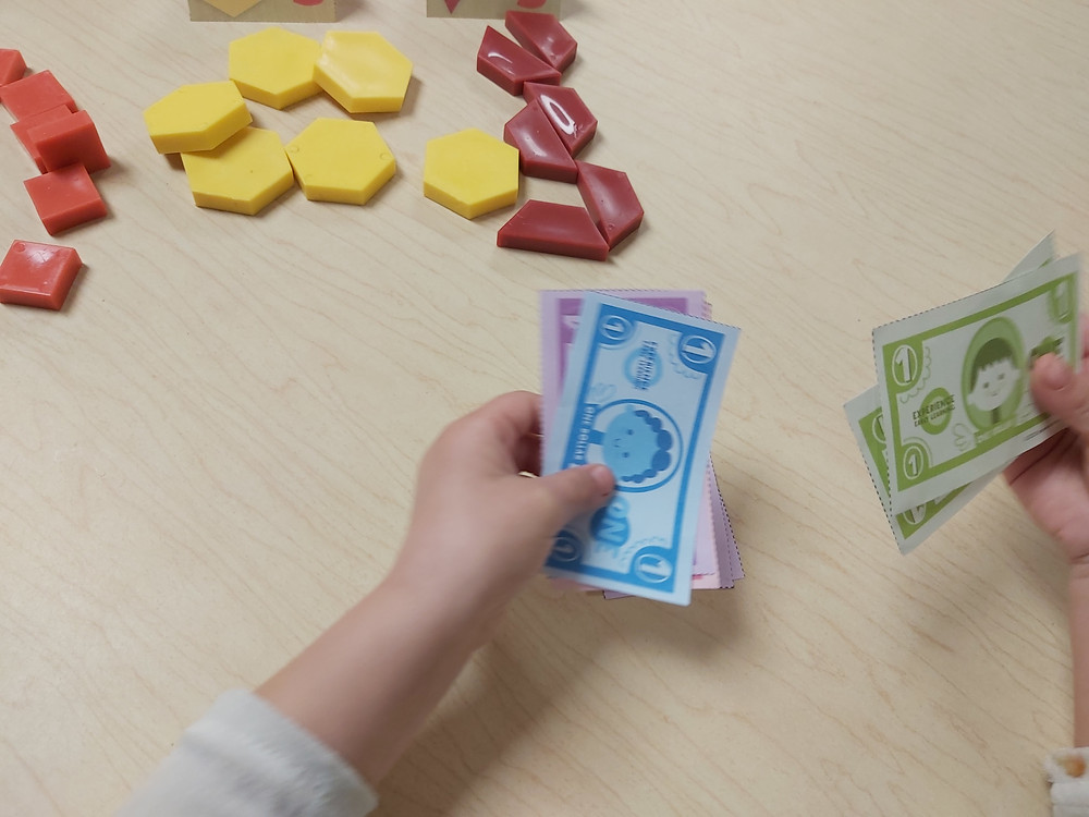 preschooler counting pretend money for mango store dramatic play