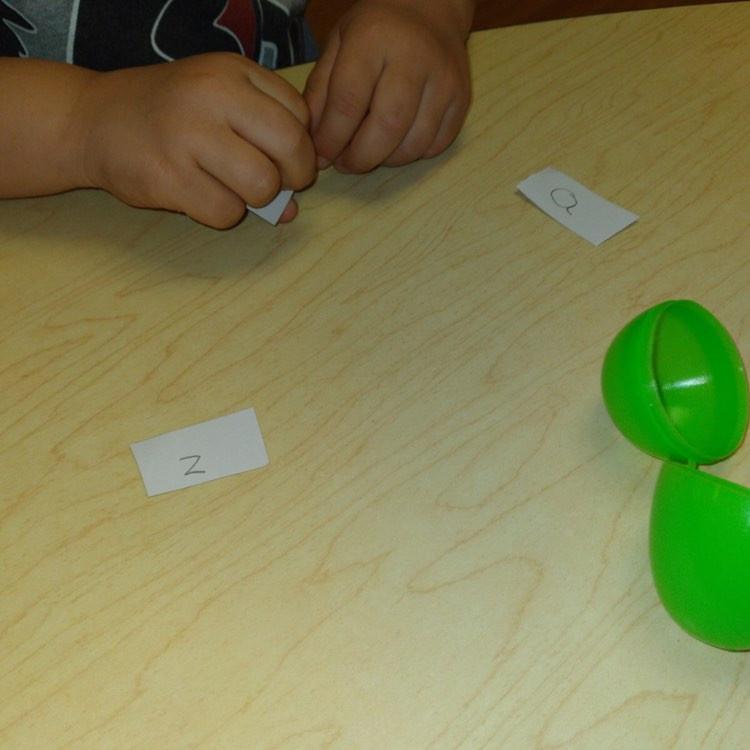 preschooler playing egg letter recognition game