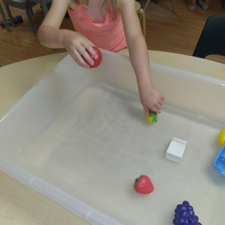 preschooler exploring play kitchen food in water sensory bin
