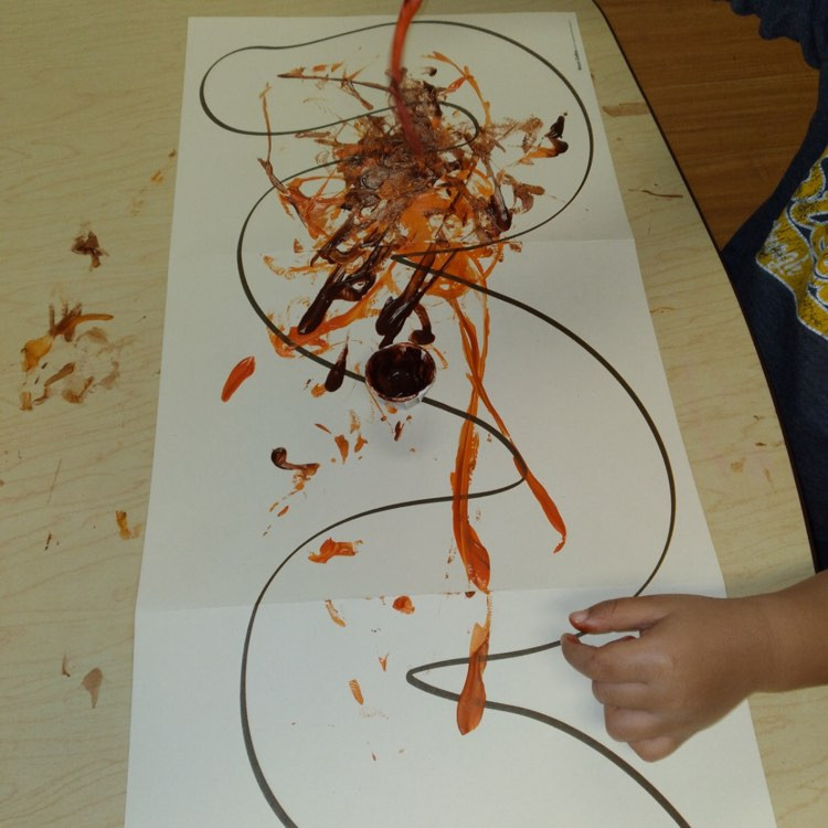 preschooler painting on worm outline using rubber worms