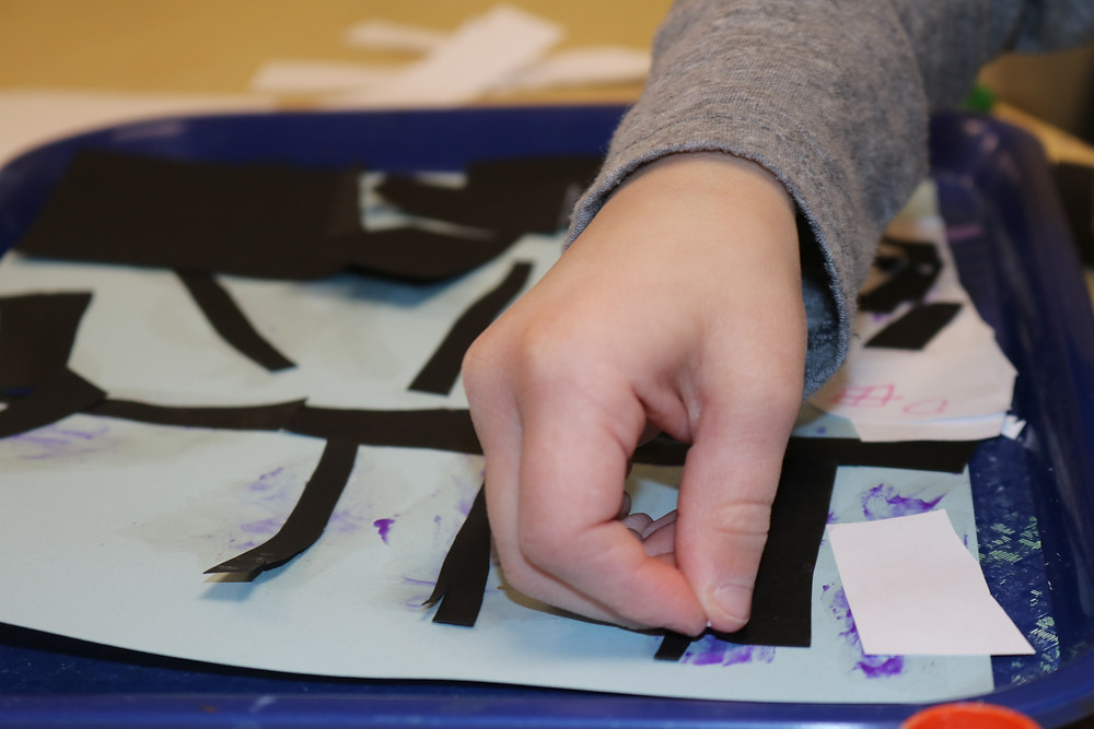 child gluing paper pieces to project