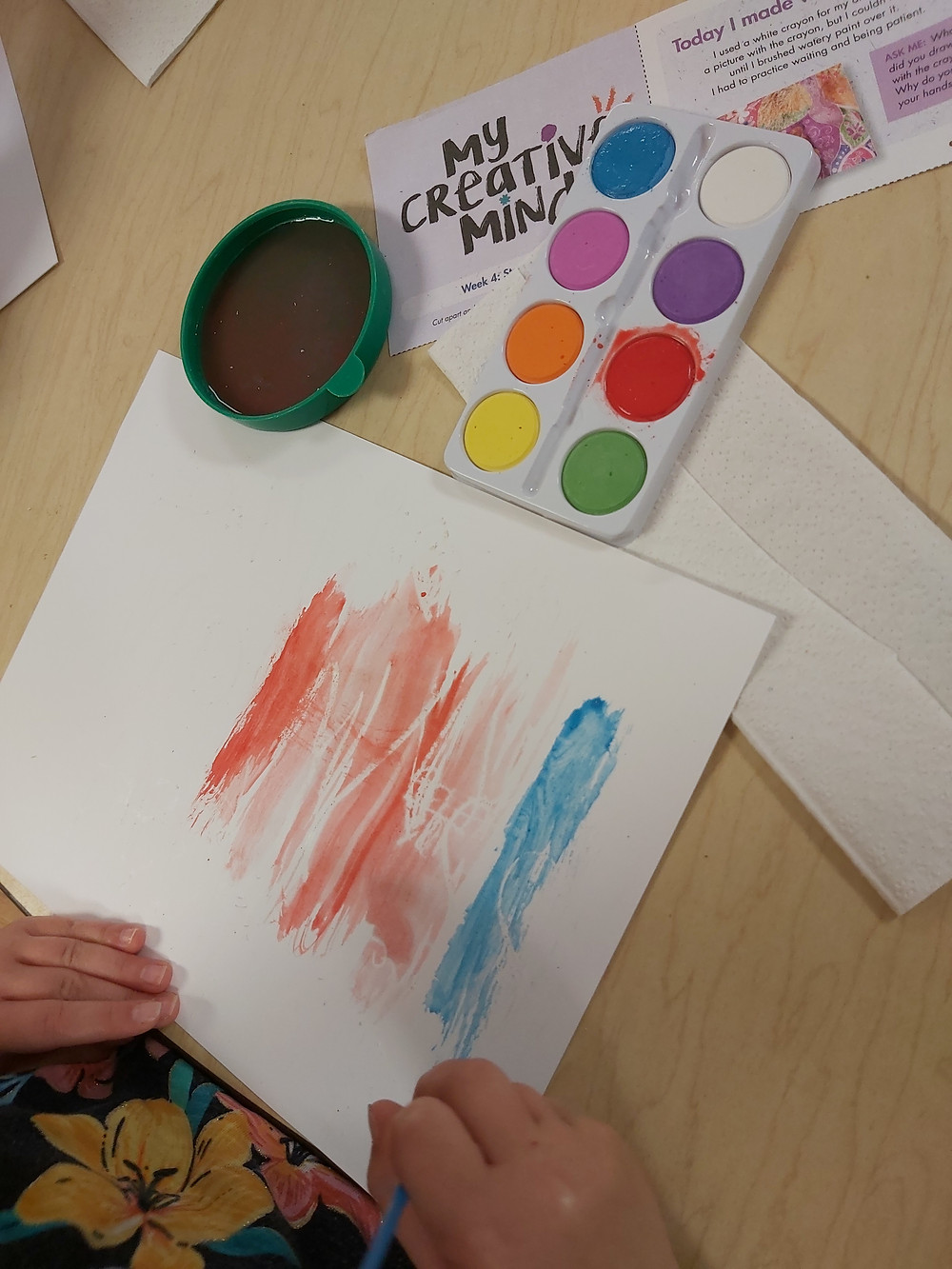 preschooler painting over white crayon with watercolor