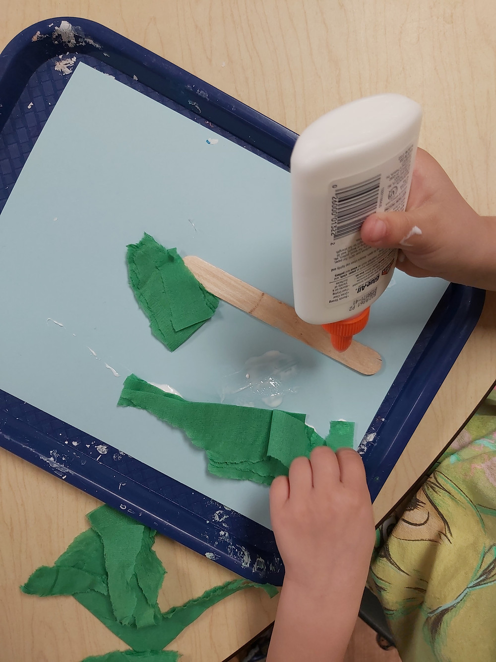 preschooler gluing craft stick on cardstock