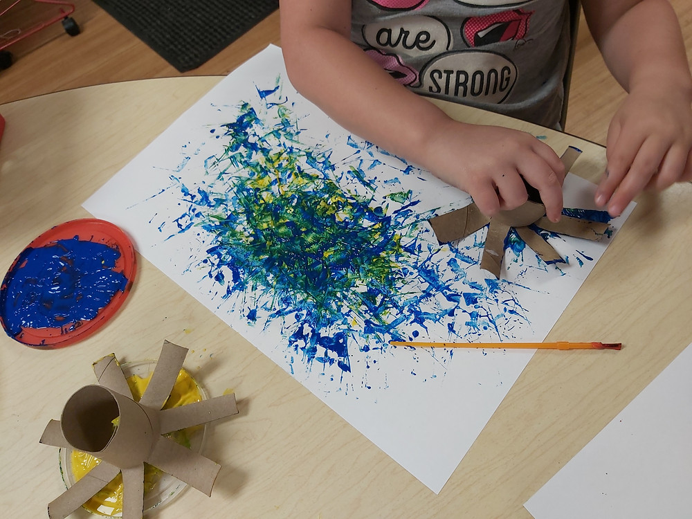 preschooler making stamped fireworks on cardstock