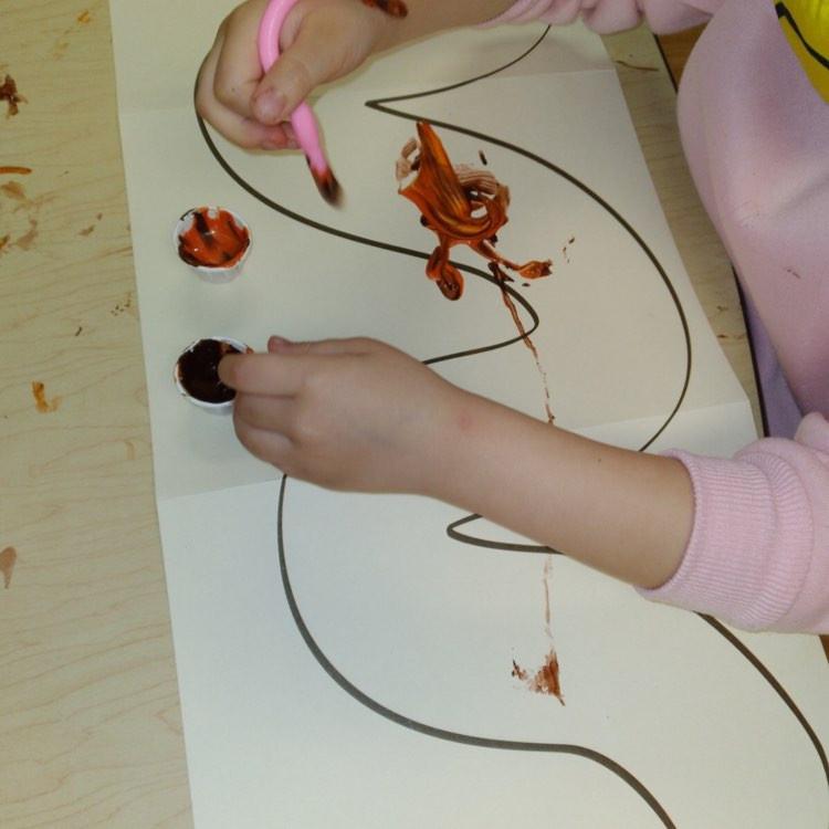 preschooler painting with rubber worm