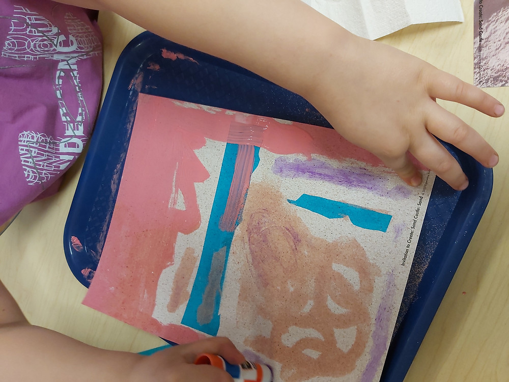 preschooler adding glue to process art