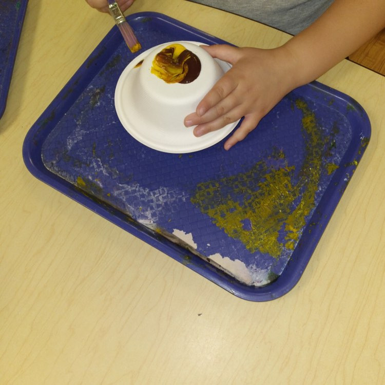 preschooler painting cardboard bowl with yellow and brown paint