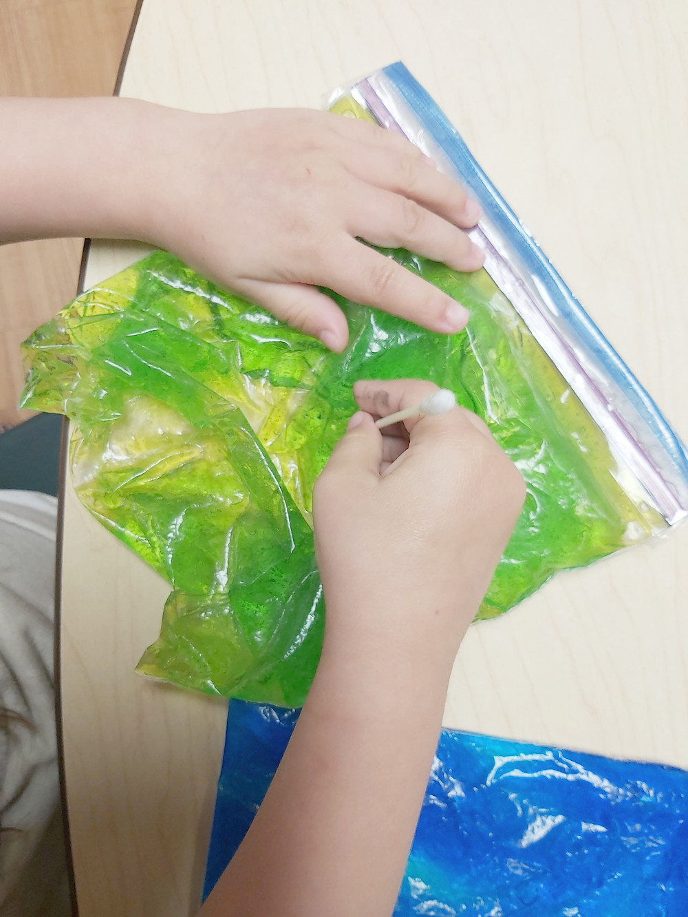 preschooler using q-tip and writing bag to form letters