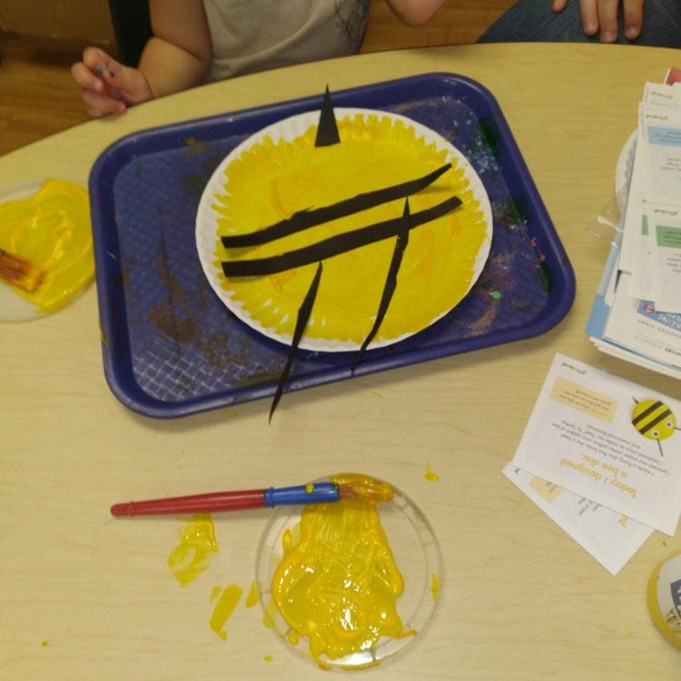 preschooler making bee disc craft using paper plate
