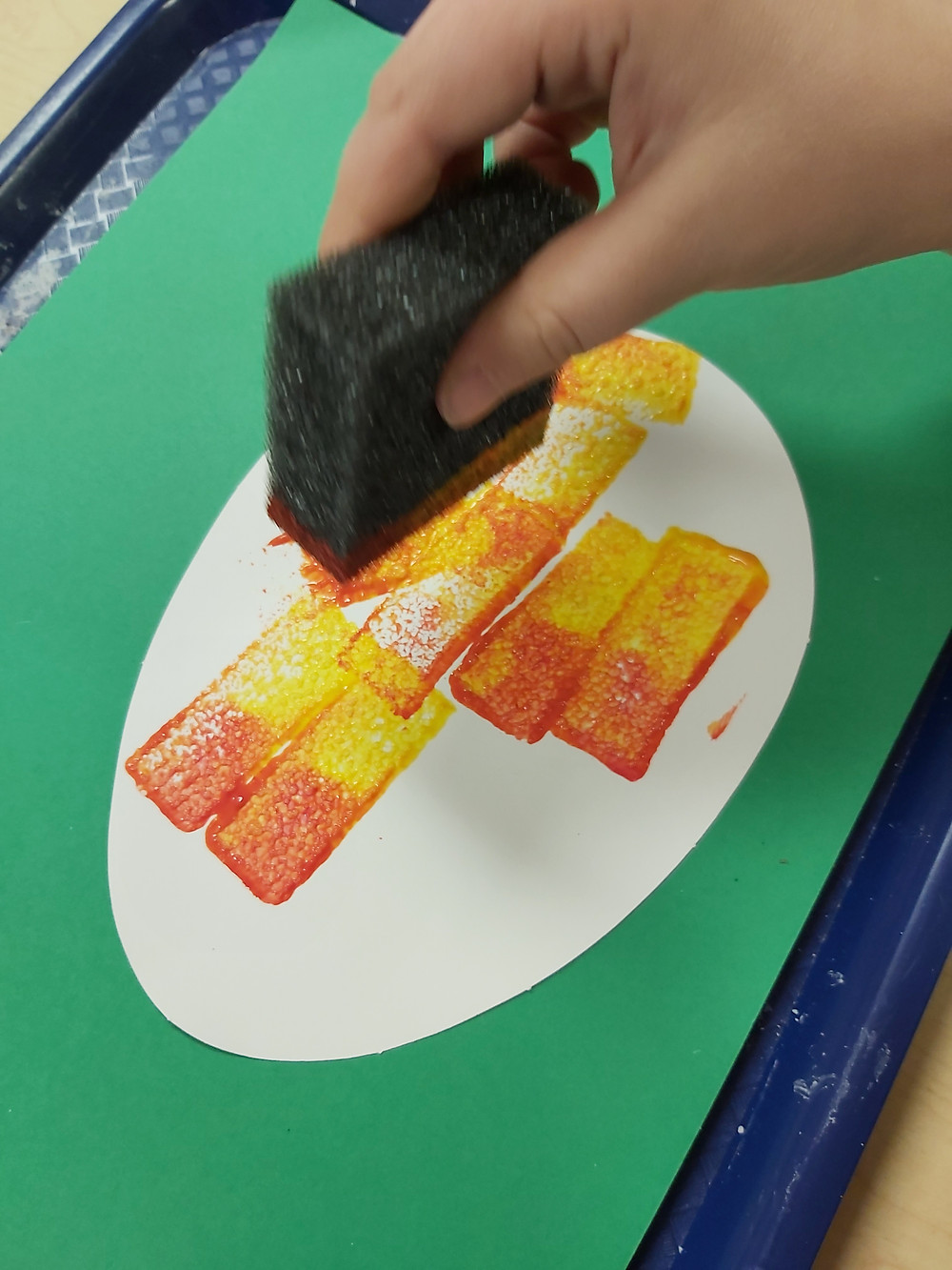 preschooler sponging red and yellow paint onto paper mango