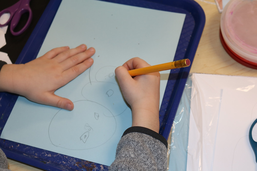 child drawing snowman with pencil