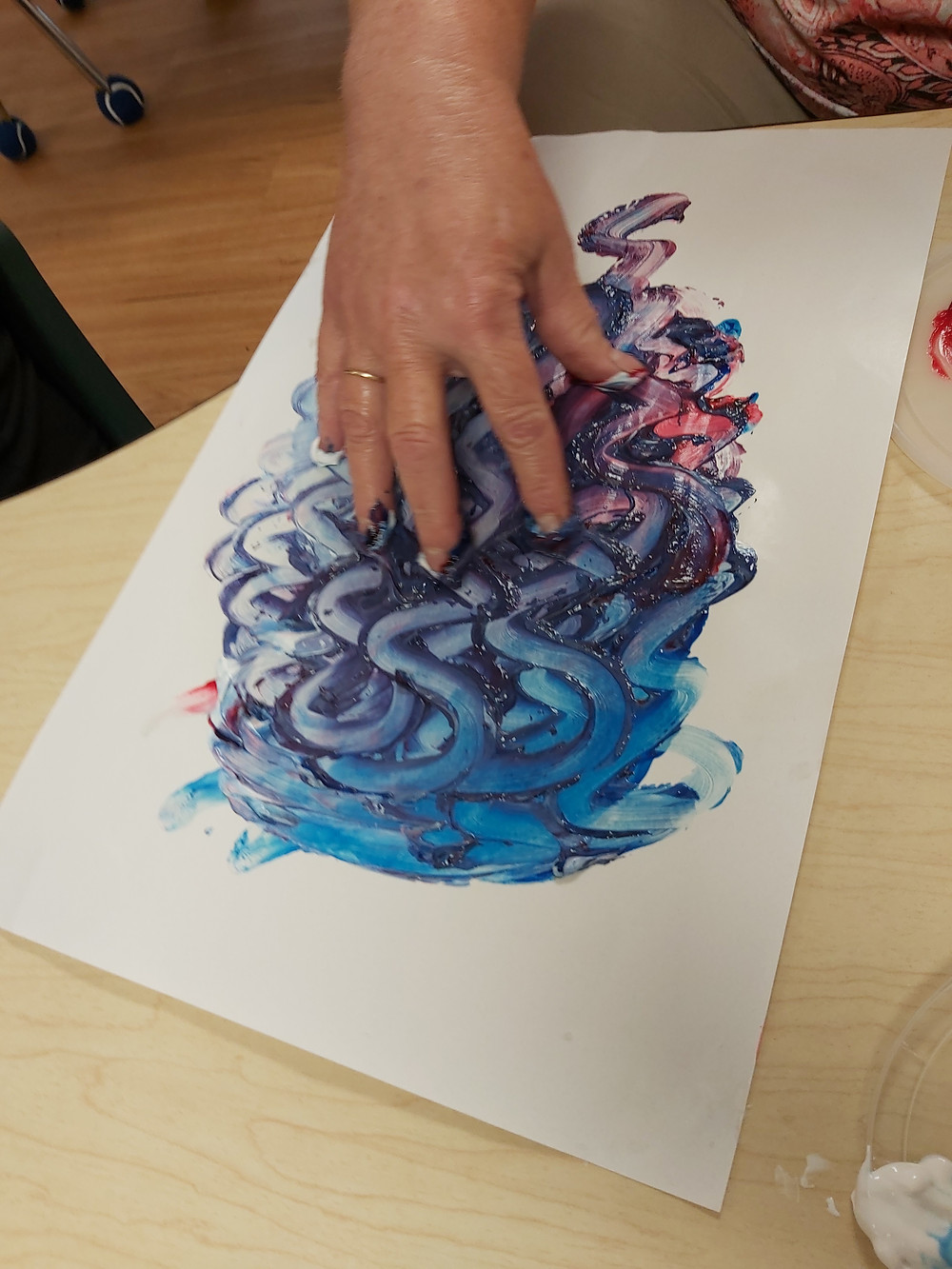 teacher demonstrating how to make designs in fingerpaint