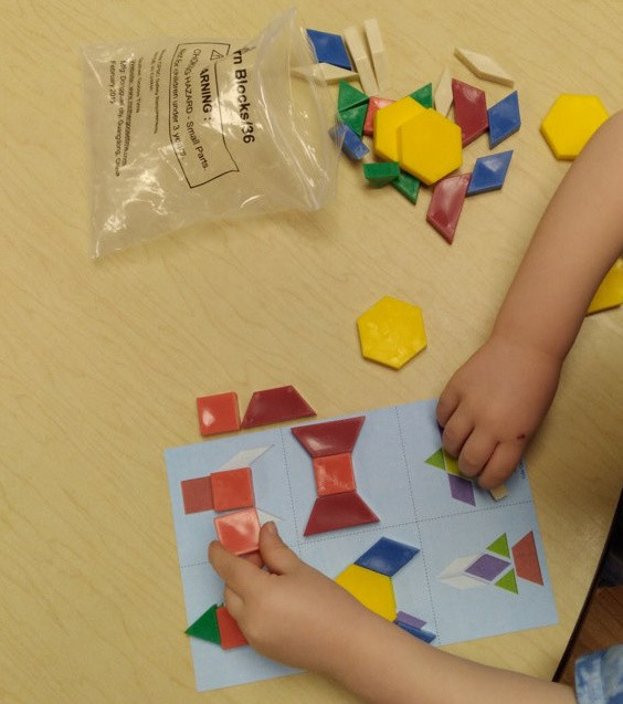 preschooler using pattern blocks to make rocket ships on design card