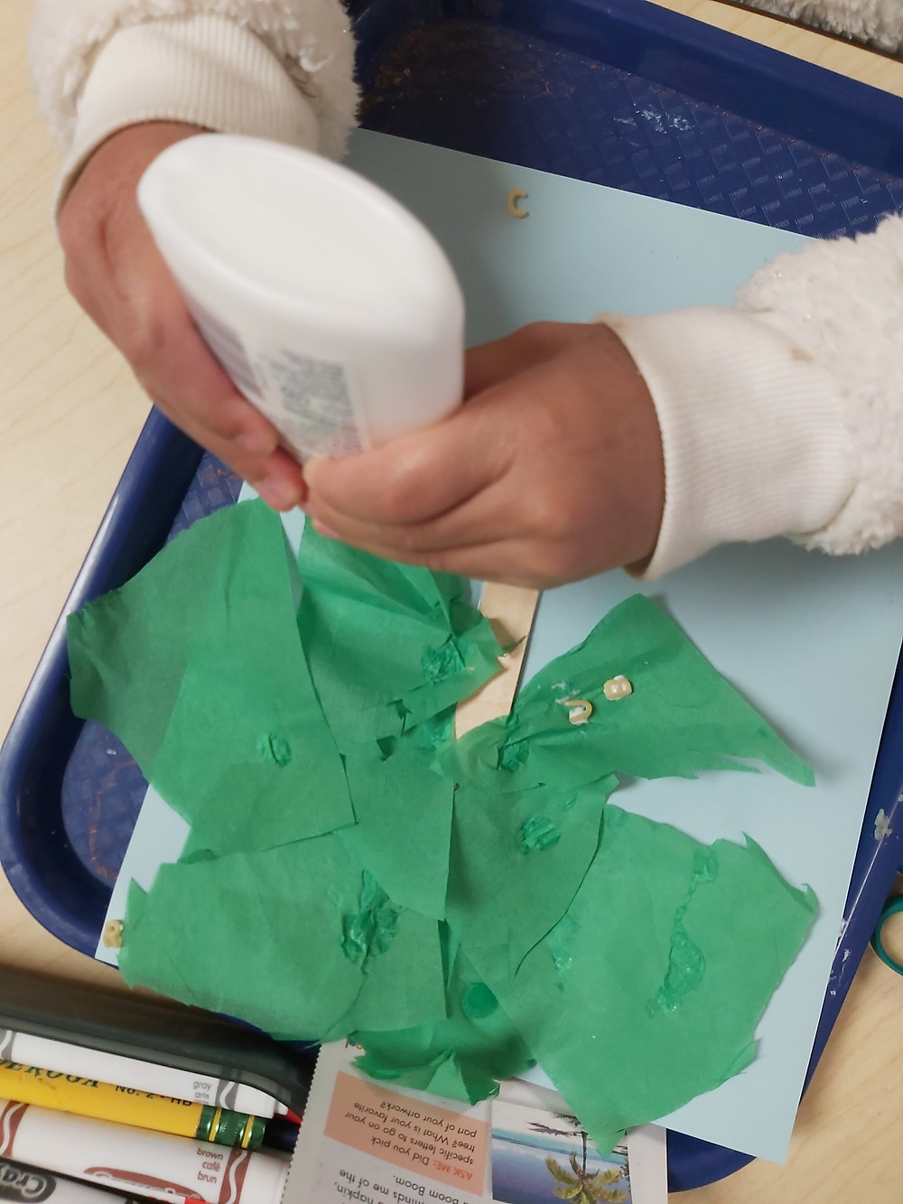 preschooler adding glue to coconut tree craft