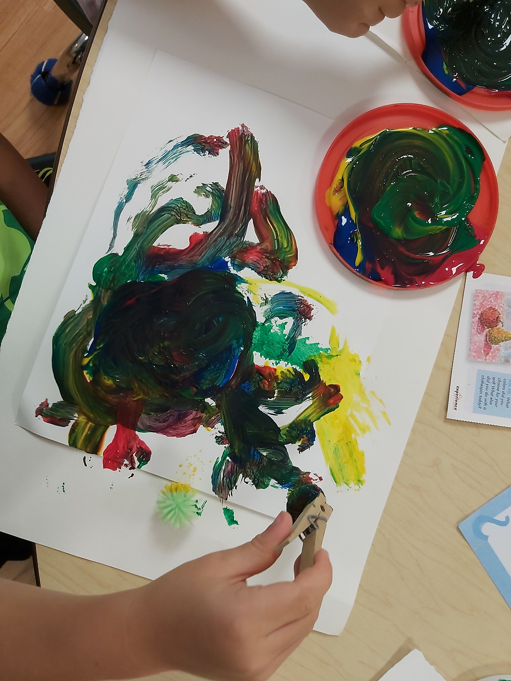 preschooler using pom-pom to paint