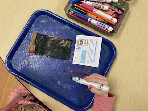 preschooler decorating small paper bag for moon rocks