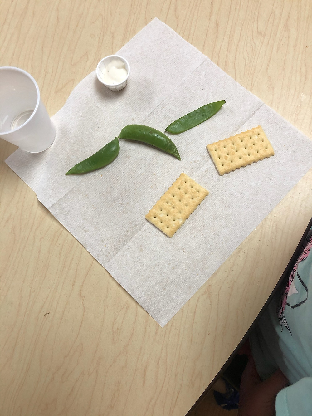 peas and crackers on napkin next to cup of water
