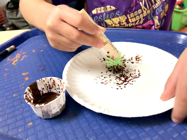 preschooler painting paper plate with pokey ball clipped to clothespin