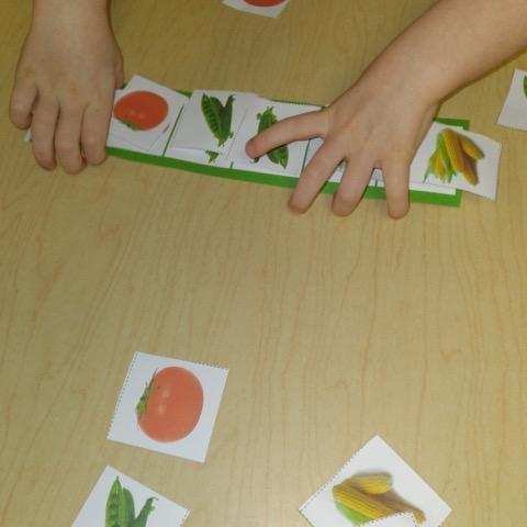preschooler making produce patterns using pattern card