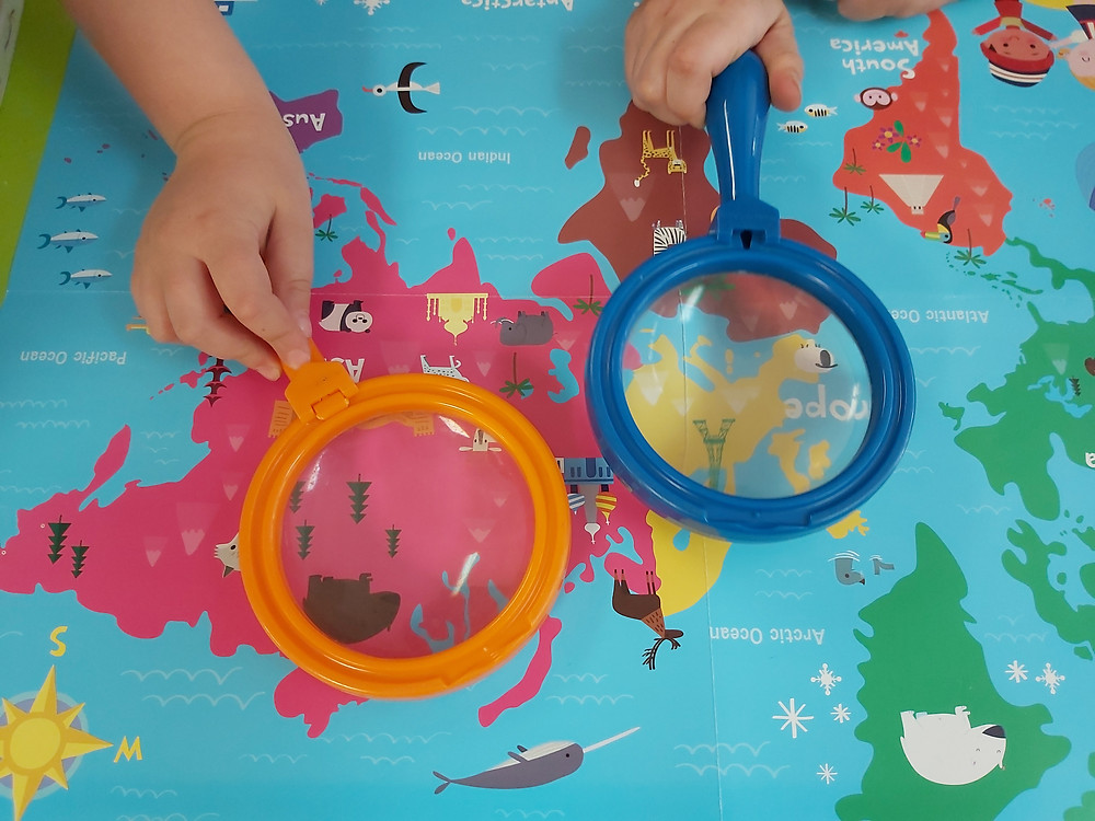 preschoolers looking at map with magnifying glasses