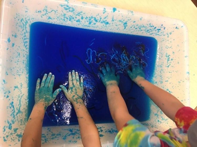 preschoolers exploring blue gel sensory bin with bits of yarn