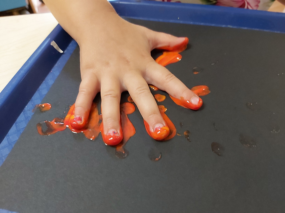 preschool making hand print with paint