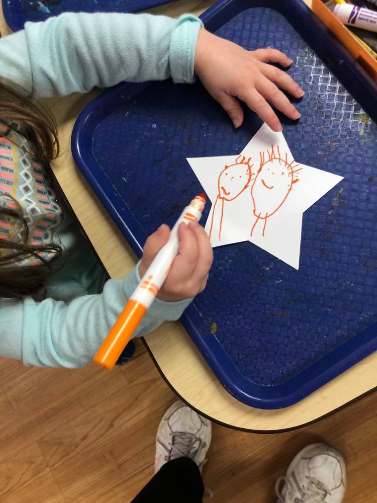 child decorating star using markers