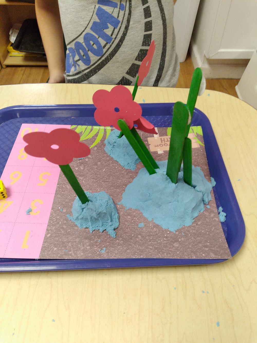 paper flowers attached to craft sticks stuck into playdough