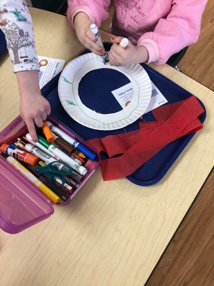 preschooler coloring on paper plate with a marker in each hand