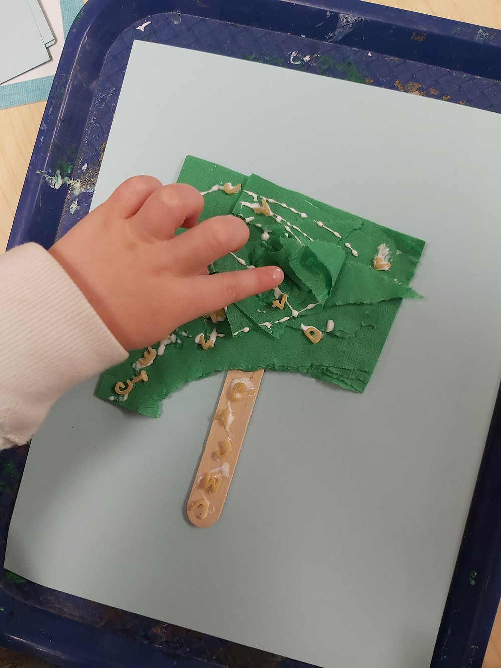 preschooler adding alphabet pasta to coconut tree craft