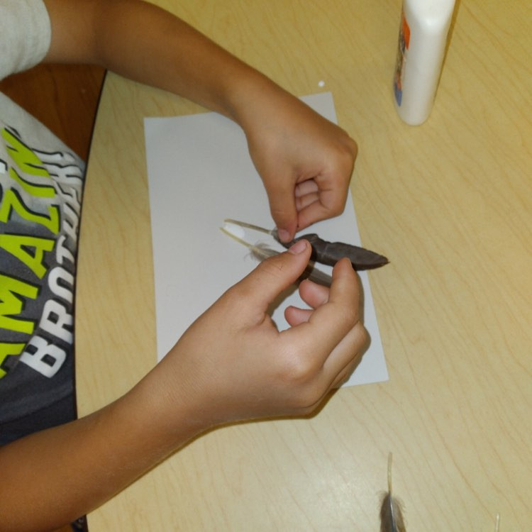 child making wing art on cardstock using feathers and glue