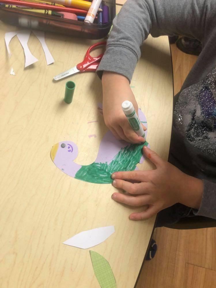 preschooler coloring Brontosaurus Puppet using markers
