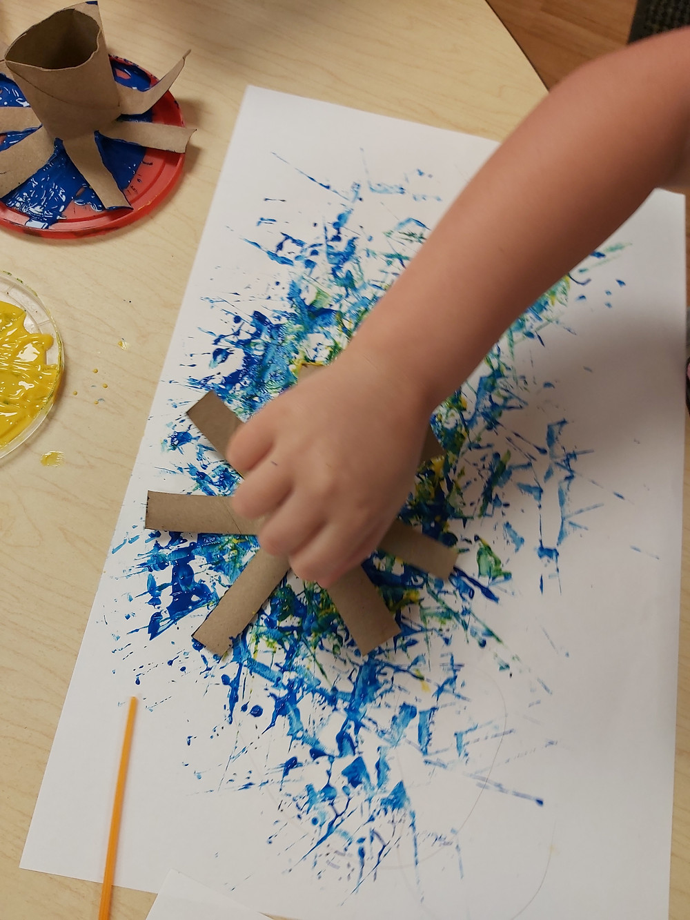 preschooler stamping cardboard tube on cardstock